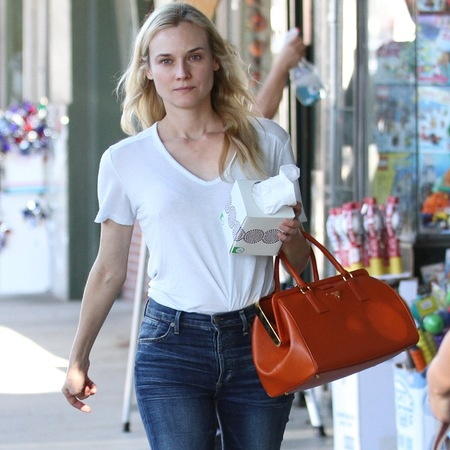 Diane Kruger carrying the Prada papaya saffiano lux bag from the Fall/Winter 2012