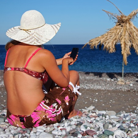 Woman on beach using mobile phone