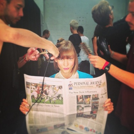 Karlie Kloss reading Wall Street Journal at NYFW SS14
