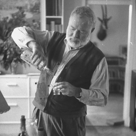 ernest hemingway - pouring himself a shot - drinking alcohol - famour writer and author - handbag.com