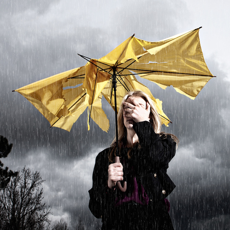 woman in rain - angry - defeated - bad hair - emergency kit and solutions to rainy hair day- handbag.com