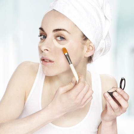 woman applying makeup - woman with hair in towel turban - getting ready - handbag.com