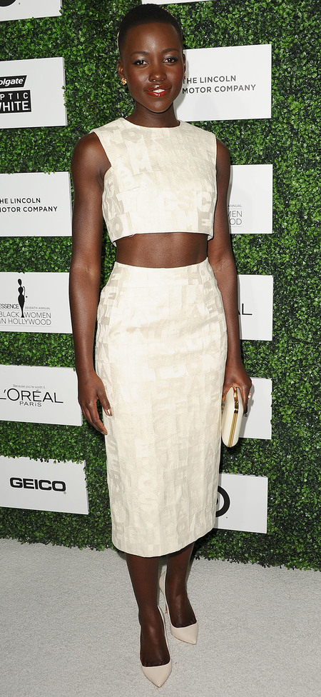 lupita nyongo in crop top and skirt - kim kardashian fashion trend - toned arms and abs - handbag.com