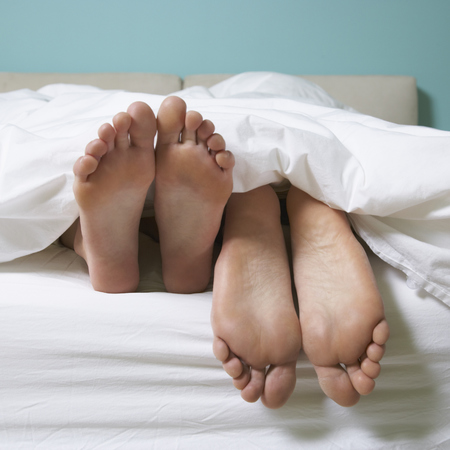 how you sleep affects relationships - feet in bed - evening bag - handbag.com
