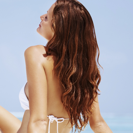 woman sitting on beach-holiday-hair-brown-coloured-sun-white bikini-handbag.com