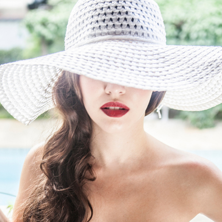 woman on holiday-beach-red lipstick-floppy sun hat-cocktail-summer style-nautical navy swimsuit-handbag.com