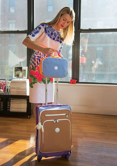 natalie joos posing with kipling suitcases - blogger natalie joos shares her travel essentials - travel bag - handbag