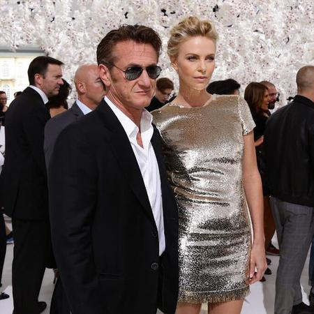 Charlize Theron and Sean Penn at Dior Couture show Paris - celebrity couples - couture fashion shows - fashion news - celebrity news - handbag.com