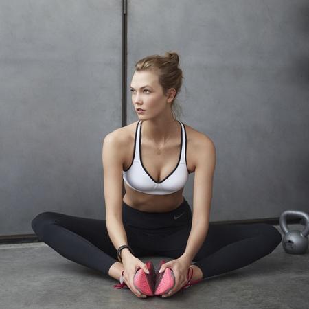 Karlie Kloss - nike performance sports bra - white bra stretching legs - handbag.com